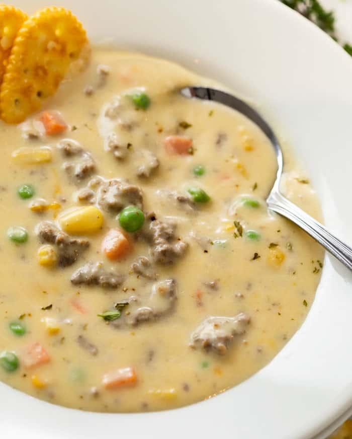 A spoon in a white bowl full of creamy Shepherd's Pie Soup.
