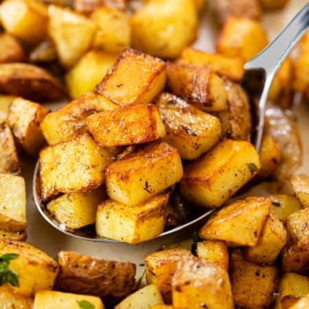 A large metal spoon full of crispy skillet potatoes.