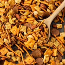 A baking sheet with spicy chex mix with a wooden spoon.