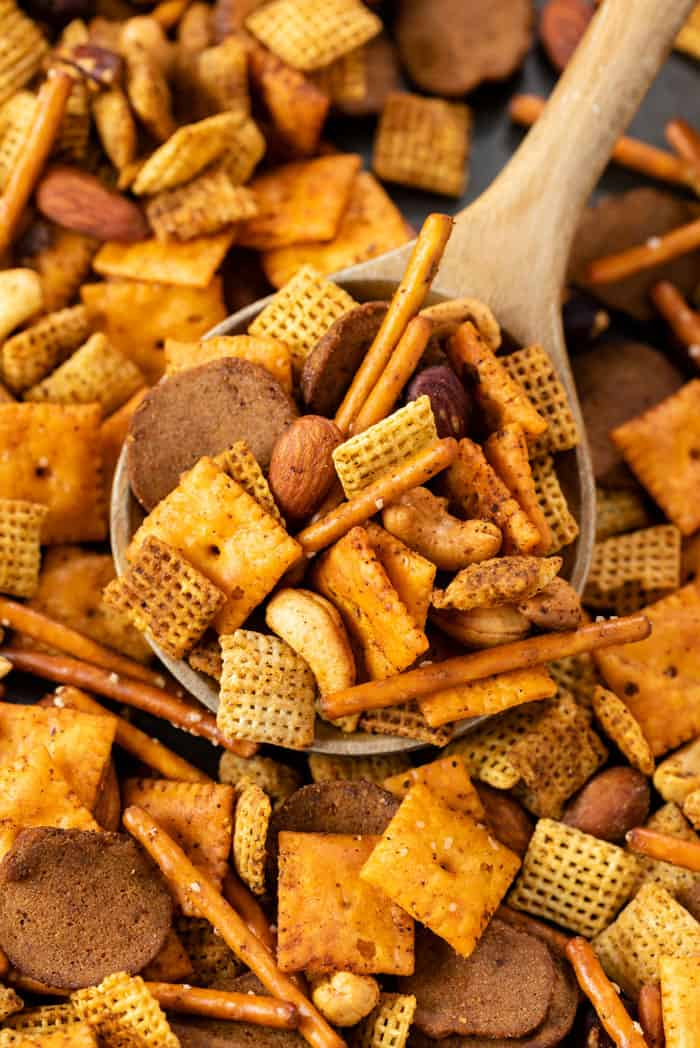 A wooden spoon scooping up Spicy Chex Mix from a baking sheet.