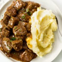 Tender Beef Tips and Gravy on a plate with Mashed Potatoes and fresh parsley.