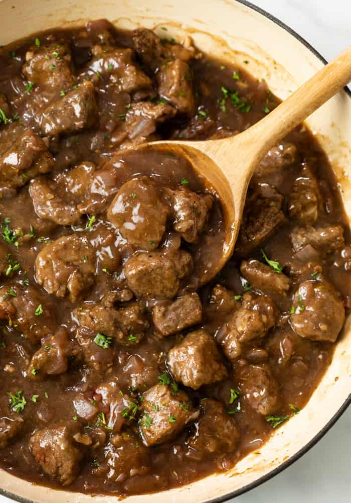A wooden spoon scooping up Beef tips in gravy in a skillet topped with fresh parsley.