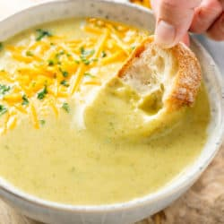 A hand dipping bread into a bowl of cream of broccoli soup.
