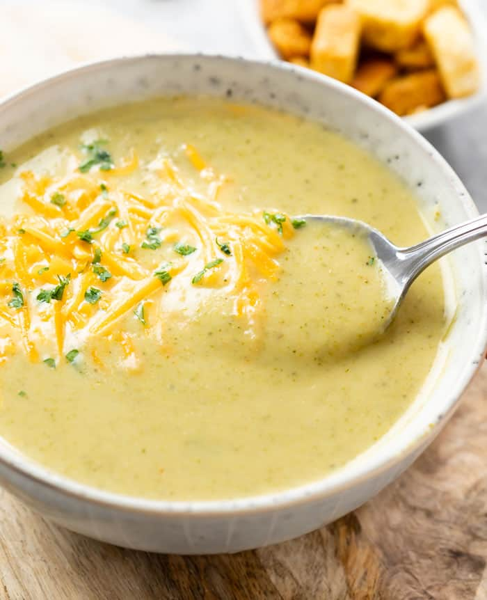 A spoon scooping up cream of broccoli soup from a bowl.