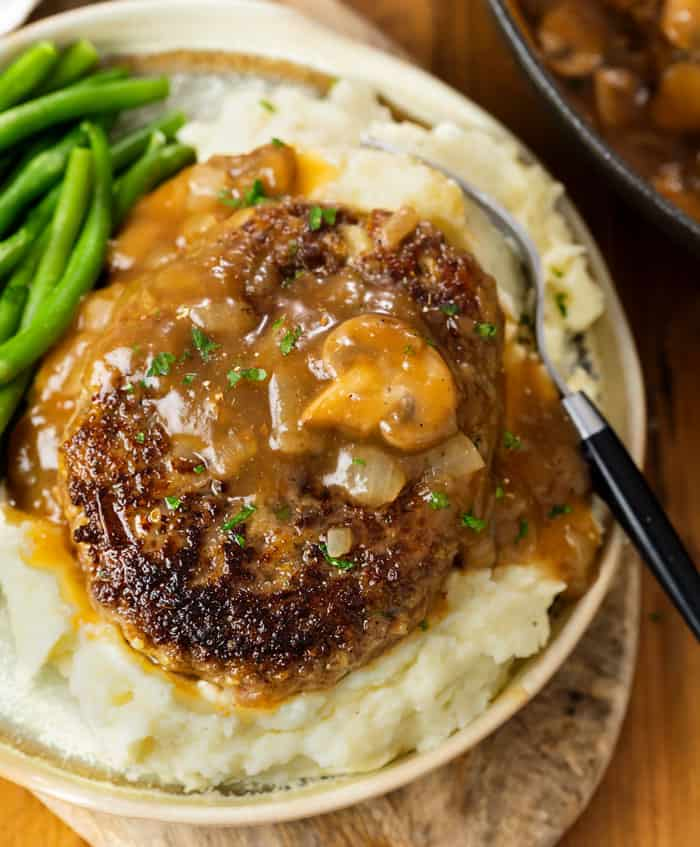 Salisbry Steak on top of creamy mashed potatoes with green beans.