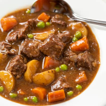 Slow Cooker Beef Stew in a white bowl with a spoon in the back.