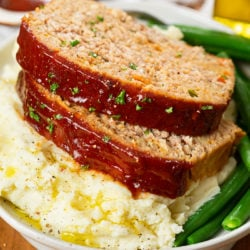Slices of turkey meatloaf on top of mashed potatoes with green beans.
