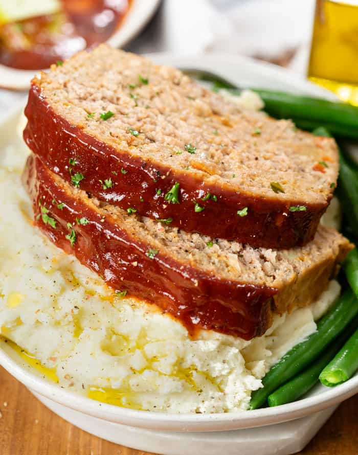 A plate with Turkey Meatloaf on top of a pile of mashed potatoes with green beans.