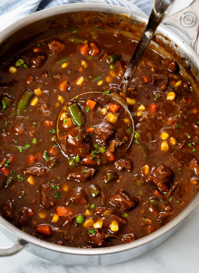 A pot filled with Beef Vegetable Soup with a ladle in it.