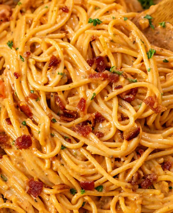 A close up view of spaghetti noodles in a creamy bacon sauce.