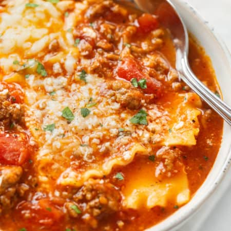 A white bowl filled with Lasagna Soup topped with cheese with a spoon in the back.