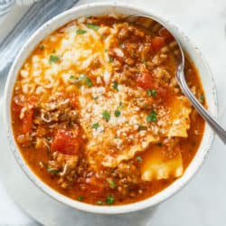 A white bowl filled with Lasagna Soup topped with cheese and a spoon on the side.