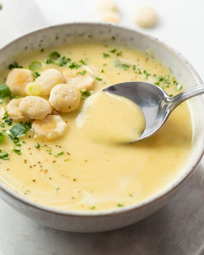 A bowl of Potato Leek Soup with a spoon and oyster crackers and parsley on the side.