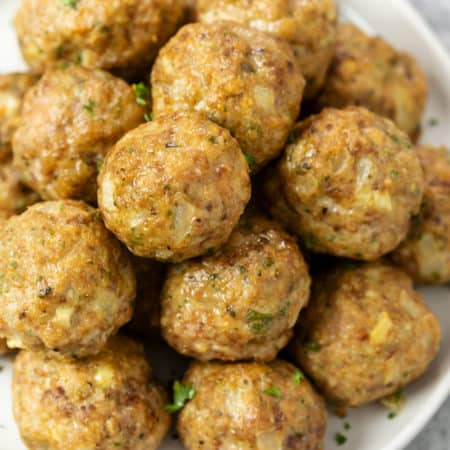 A pile of turkey meatballs on a white plate with parsley.