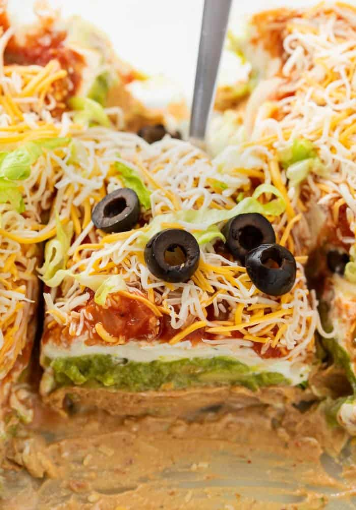 A spatula scooping up 7 layer dip from a casserole dish.