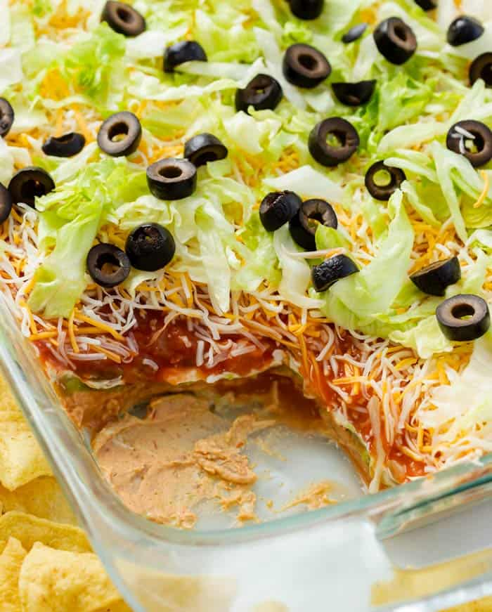 A glass casserole dish filled with 7 layer dip.