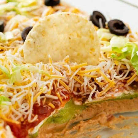 7 layer dip with a tortilla chip in it.