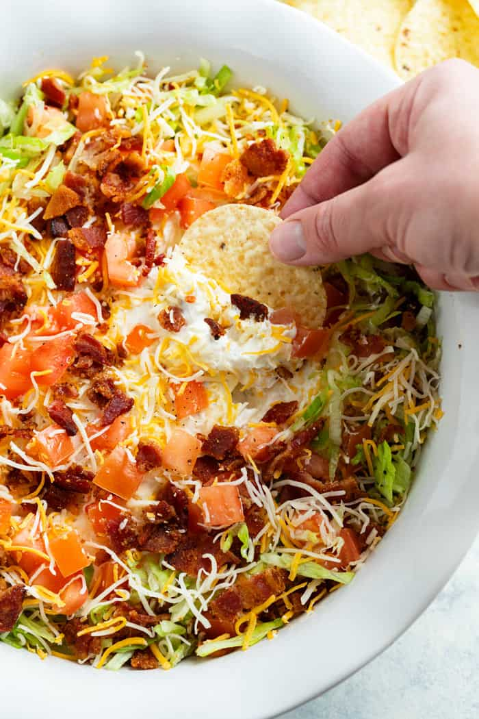 This BLT Dip is an easy appetizer idea that is served cold with chips, bread, or vegetables! It starts with a sour cream/cream cheese mixture with Ranch seasoning topped with bacon, lettuce, tomatoes, and cheese!