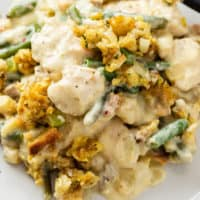 A plate with chicken and stuffing casserole with green beans and creamy sauce.
