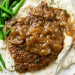 Cube Steak smothered in brown gravy with onions on a pile of mashed potatoes.