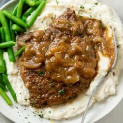 A pile of mashed potatoes topped with cubed steak with brown gravy and onions with green beans on the side.