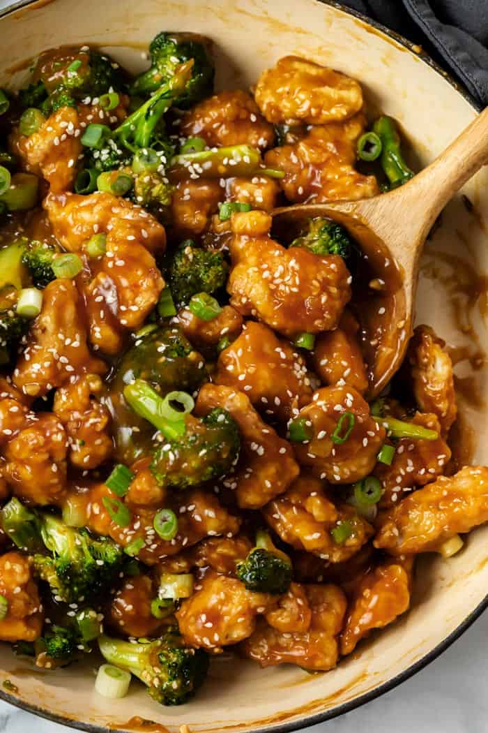 A skillet filled with General Tso's Chicken with broccoli.