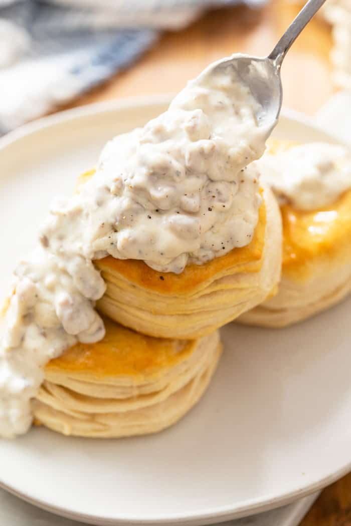 A white plate with 3 flaky biscuits with a spoon drizzling sausage gravy on top.