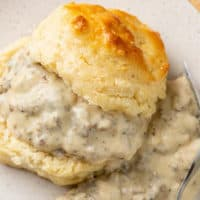 A buttermilk biscuit sliced in half with Sausage Gravy in the middle and on the side.
