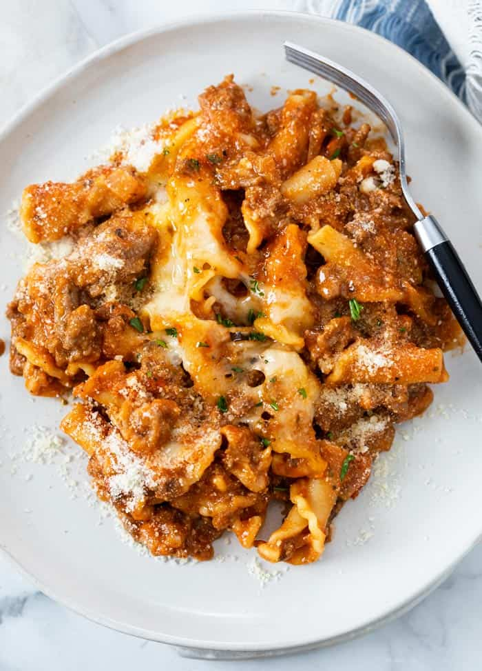 A white plate with Skillet Lasagna and melted cheese with a fork on the side.