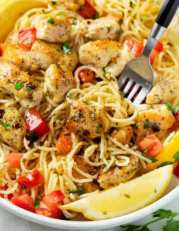 A fork in a bowl filled with chicken scampi with fresh tomatoes, parsley, and sliced lemon.