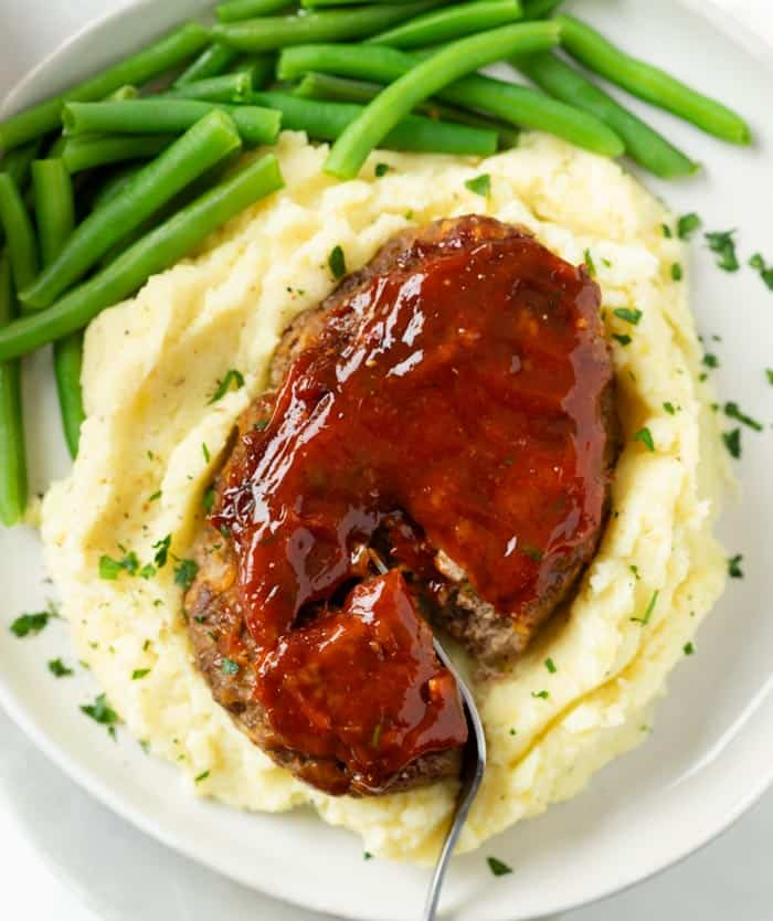 Mini Meatloaf topped with glaze on a pile of mashed potatoes with green beans.