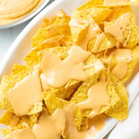A white platter with tortilla chips topped with Nacho Cheese Sauce.