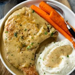 A white plate with Pork Chops in Gravy with carrots and mashed potatoes.