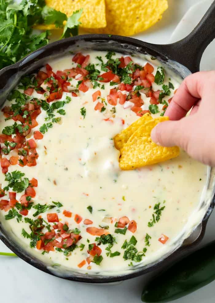 A hand dipping a tortilla chip into a skillet of White Queso Dip topped with Pico De Gallo and Cilantro