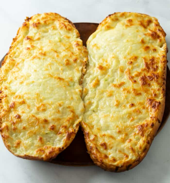French bread topped with Garlic Butter and Melted Cheese before slicing to make Garlic Bread with Cheese.