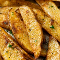 A pile of Baked Potato Wedges topped with parsley and seasoning.