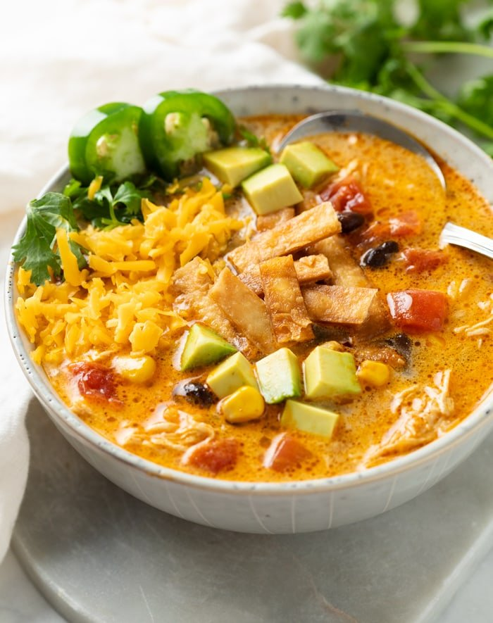 A bowl of Creamy Chicken Tortilla Soup topped with crispy tortillas, diced avocado, shredded cheese, jalapenos, and cilantro.