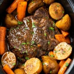 A Crock Pot Roast in a Crock with Potatoes, potatoes, and gravy.