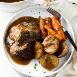 A white plate with Crock Pot Roast with gravy on top with potatoes and carrots.