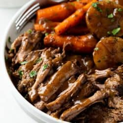 A white plate with tender Crock Pot Roast with gravy and carrots and potatoes in the background.