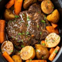 A Crock Pot Roast in a Slow Cooker with potatoes and carrots with gravy.