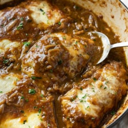 A skillet of French Onion Chicken in a dark sauce with caramelized onions and melted cheese.