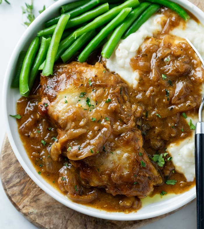 A plate with French Onion Chicken with mashed potatoes and green beans.