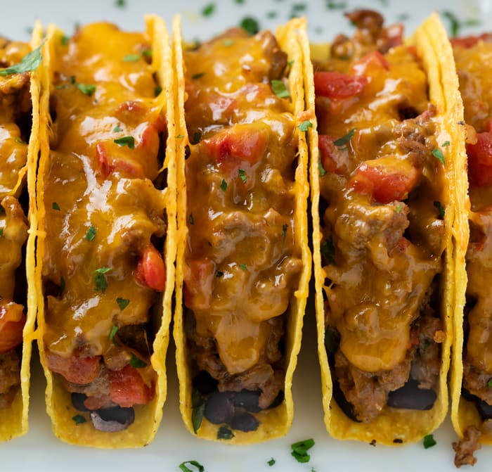 Baked Tacos filled with a creamy ground beef mixture with melted cheese lined up in a casserole dish.