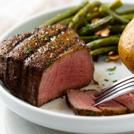 A medium rare filet mignon with a slice cut into it and green beans in the background.