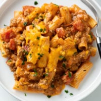 Ground Beef Casserole on a white plate topped with melted cheese.