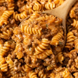 A wooden spoon scooping up ground beef pasta from a skillet.