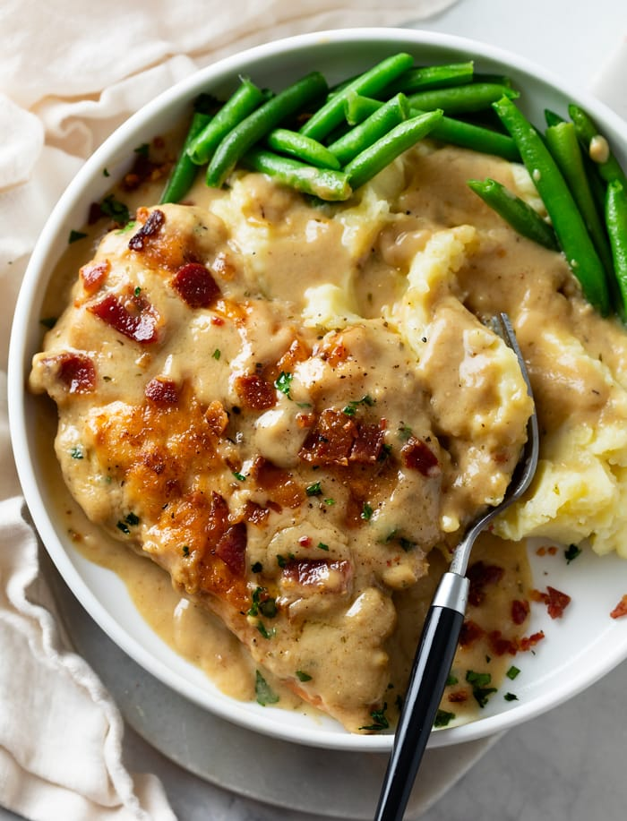 A white plate with Smothered Chicken next to mashed potatoes with gravy and green beans.