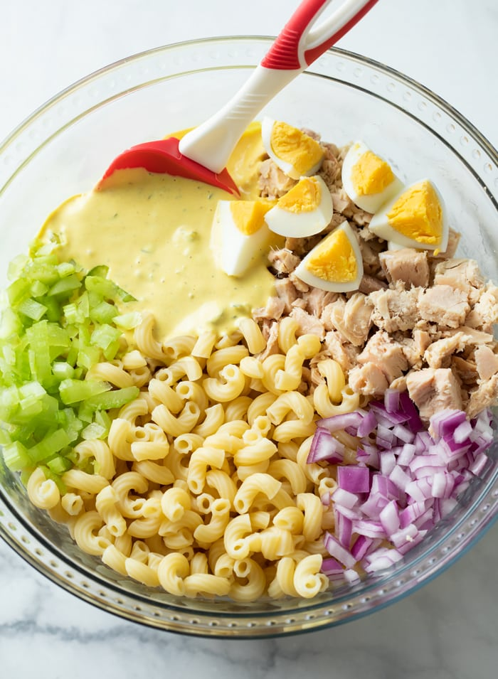 A glass bowl with ingredients for making Tuna Pasta Salad before being stirred.