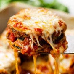 Cheesy Zucchini Parmesan with Marinara sauce and strings of cheese hanging down.